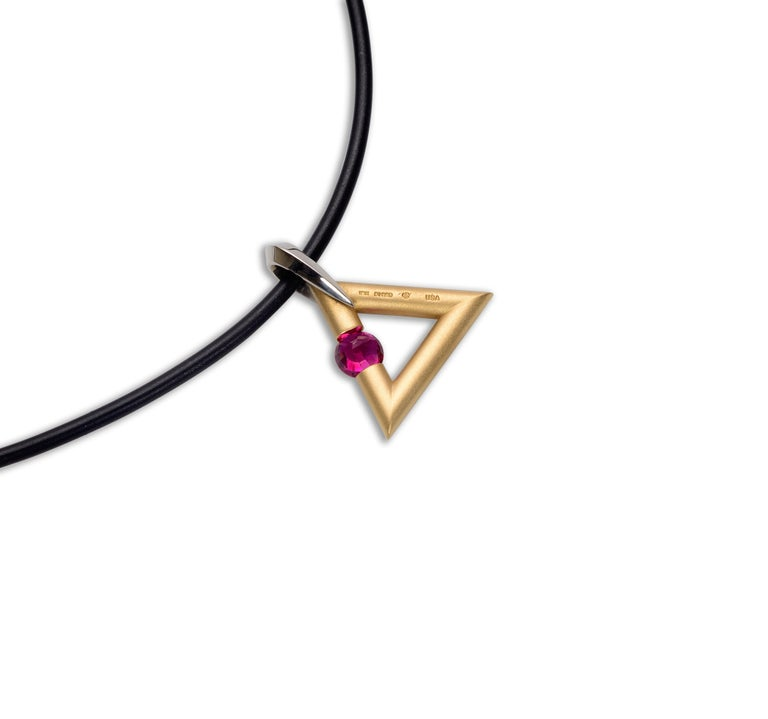 The Steven Kretchmer Logo/Triangle Shaped Pendant with a tension-set ruby is handcrafted in a matte 18K yellow gold with a shiny platinum bail. The reddish pink round cut 0.63ct ruby is tension-set in the side of the triangle shape. This pendant is