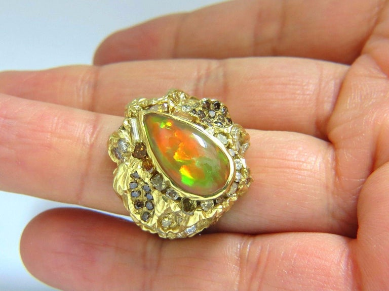 6.00CT Natural Opal Ring.  Cabochon Pear Shaped  VS clean clarity  Brilliant rays of orange, greens and some reds.  A true holographic effect  Opal is NOT a dublet  17 X 8 mm    6.25ct. diamonds  Rounds and full cuts.  Mix of natural fancy browns
