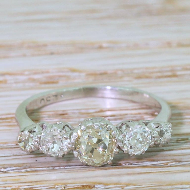 A delightfully unique vintage five stone ring. The centre stone – weighing approximately 0.70 carat – is bright, internally clean and displays a clear, light yellow tone – with the whiteness of the four diamonds either side emphasising the colour of