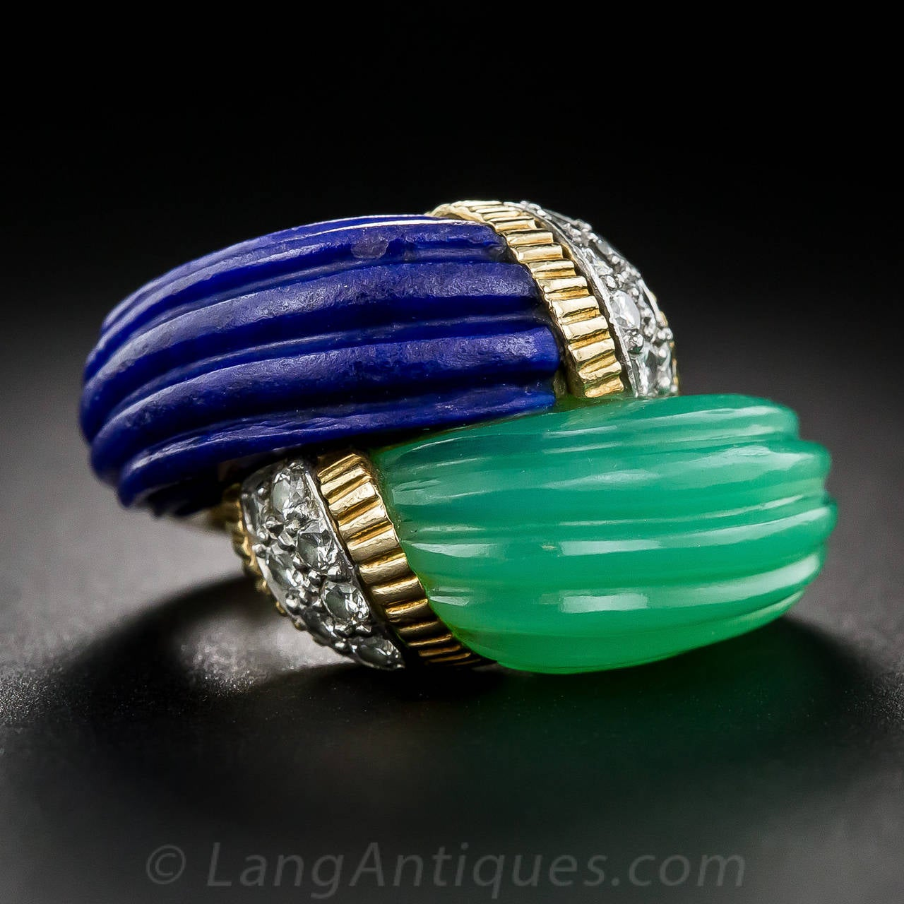 A gem-quality, glass-like, royal-blue lapis lazuli snuggles up close to a mirror-image, bright apple-green chalcedony (a.k.a. chrysoprase), both handcarved in a sweeping wave-like shape with a classic fluted texture. Both pieces are crowned with a