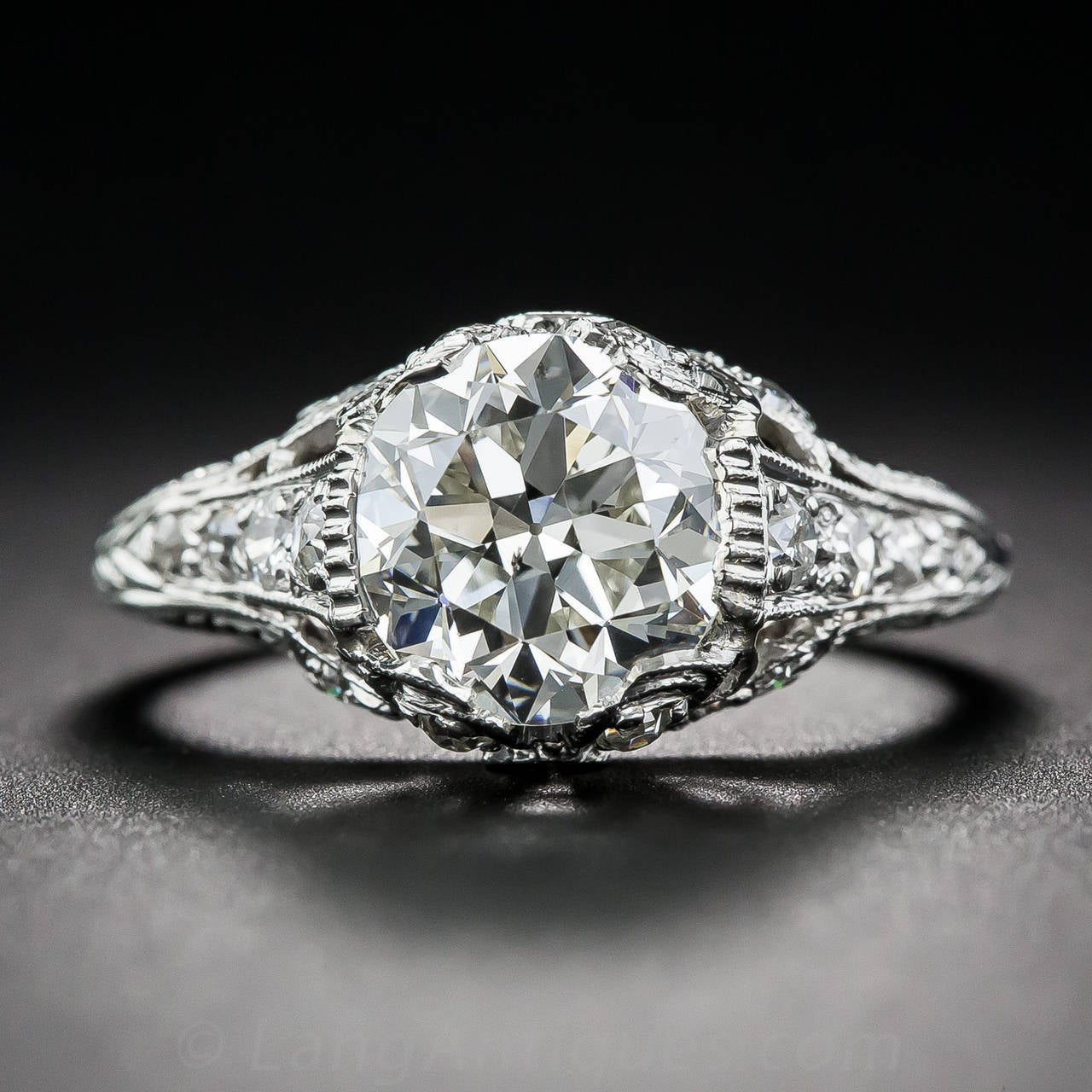 An absolutely gorgeous European-cut diamond, weighing 2.09 carats, beams brilliantly from within an original platinum and diamond mounting dating from the early-twentieth century. The splendid ring, which you can tell from the all around hand
