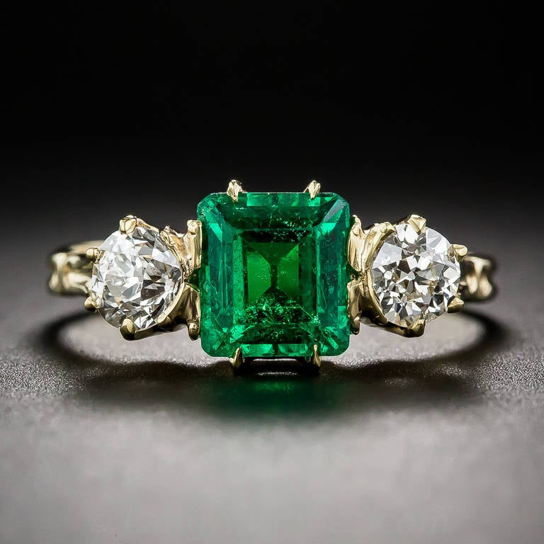 A rich luscious green and crystalline old mine square emerald-cut emerald, weighing 1.35 carats, shines shoulder-to-shoulder with a pair of sparkling old mine-cut diamonds, weighing .35 carat each (.70 carats total), in this truly superb and