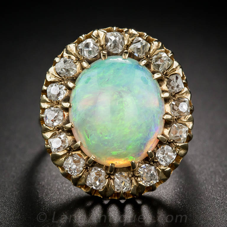 A gorgeous, large-scale (7/8 by 3/4 inch) Victorian cabochon opal and diamond ring. This 7.45 carat opal glows with an enchanting play of blues and greens with flashes of orange overtones. The high-cabochon gemstone is framed by sixteen sparkling