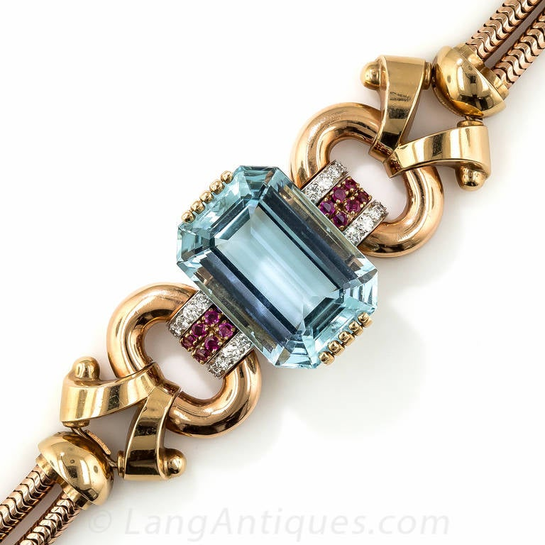 This strikingly stunning rose gold Retro bracelet by Tiffany & Co. presents a gorgeous, sizable (46.00 carat) and beautifully modeled emerald-cut aquamarine with a rich, even sky blue color. The enchanting gemstone glistens between a pair of ruby