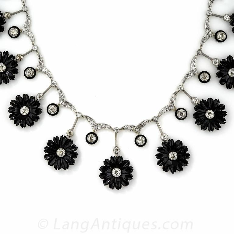 A unique and supremely beautiful late-Edwardian/early-Art Deco necklace in glorious black & white. 15 hand carved, diamond centered onyx flowers alternate with black enamel outlined European-cut diamonds, all of which suspend from a glittering