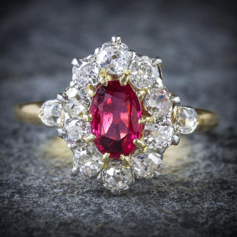 This stunning antique Ruby and Diamond cluster ring is Victorian, Circa 1900  A rich, red 0.75ct Ruby sits in the centre surrounded by a halo of sparkling Diamonds  There are 0.75ct of Diamond in total with a smaller 0.10ct Diamond on each shoulder