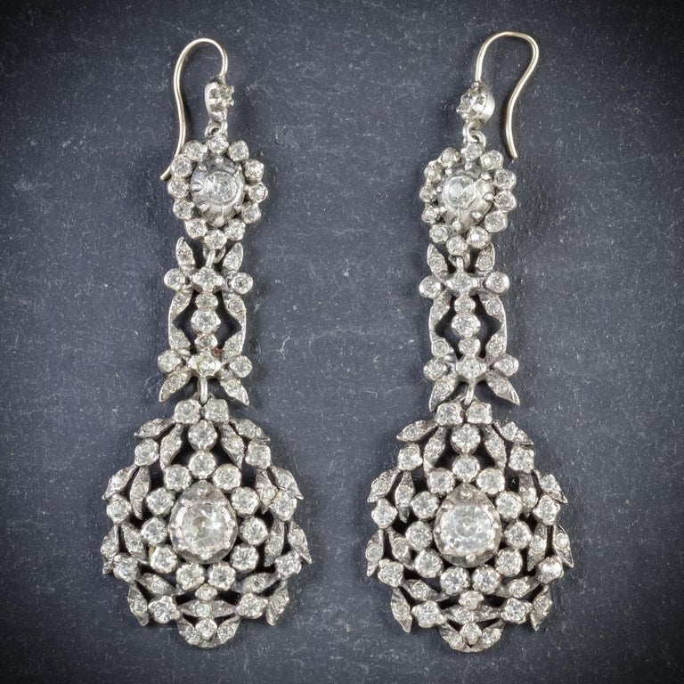 This fabulous long pair of antique triple drop earrings are Georgian, Circa 1800  Each earring is decorated in sparkling white Paste Stones - approx. 5ct across each earring  Set in Silver and fitted with 18ct Yellow Gold shepherd hook wires  A