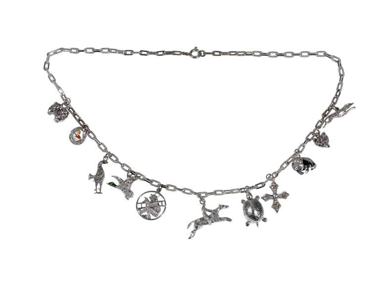 18kt white gold link bracelet supporting 11 charms including a fox, dog,tortoise,cross,horse,phaesant,bird,jockei and variously decorated with small single-cut and rose-cut diamonds and carved applied with various colors of enamel, length 15.6