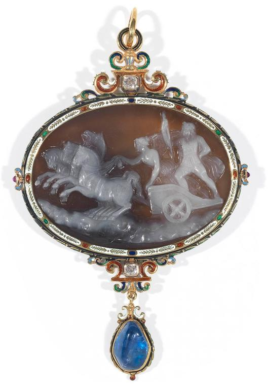 The large  hardstone cameo carved to depict Nike, the Victory driving the chariot with Jupiter, within a frame decorated with multicolored enamels accented by two rubies at the sides,  at the top an enamel scroll decoration centered by an old cut