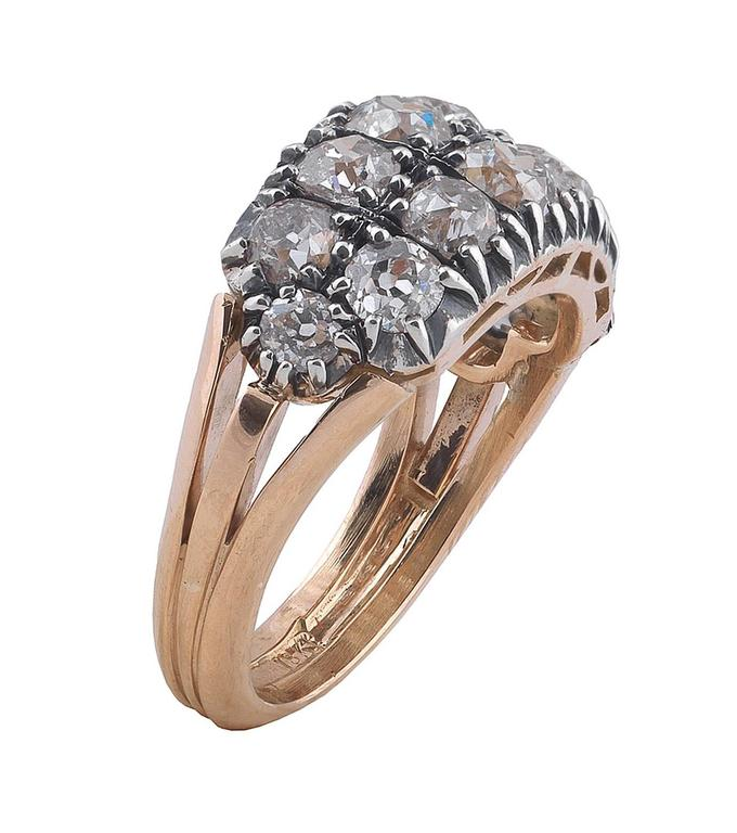 Designed as an half loop two rows cluster ring, the claw set old cut diamonds weighing approximately 3.60 cts, to a carved gallery and trifurcated plain hoop.  Mounted in silver and 18Kt gold.  Finger size: 7 1/4  Weight: 7.4 gr
