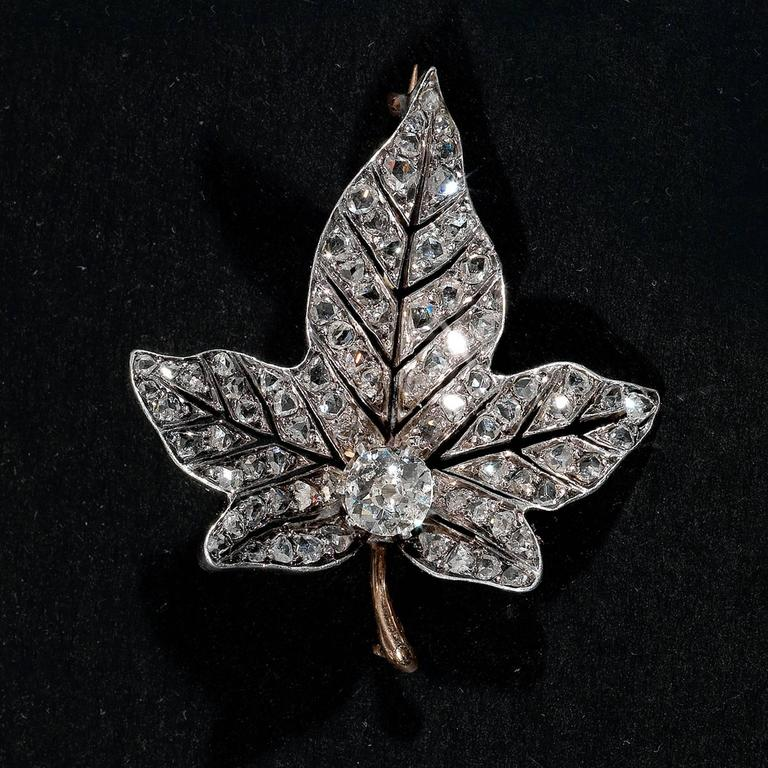 Designed with four stylized ivy leaves cluster spray, the bigger detachable for wearing separately, each centered by claw set old cut diamond and buds all seemingly from a single stem, the leaves open set throughout with rose cut diamonds.  French