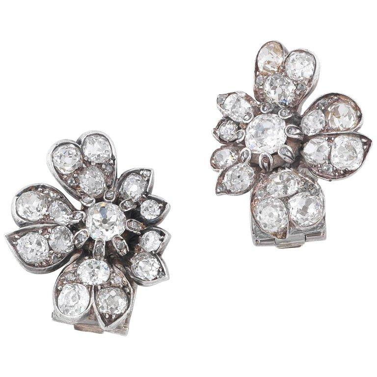 Of flower design set throughout with old cut diamonds weighing approximately 7 cts overall  Mounted in silver and gold  Clip closing back  Dimensions: 2.5 cm long, 2 cm wide   Weight: 12 gr