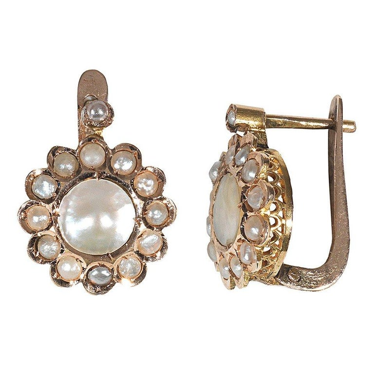 The collet set central mother-of-pearl to a border of pearls.  Mounted in yellow gold.