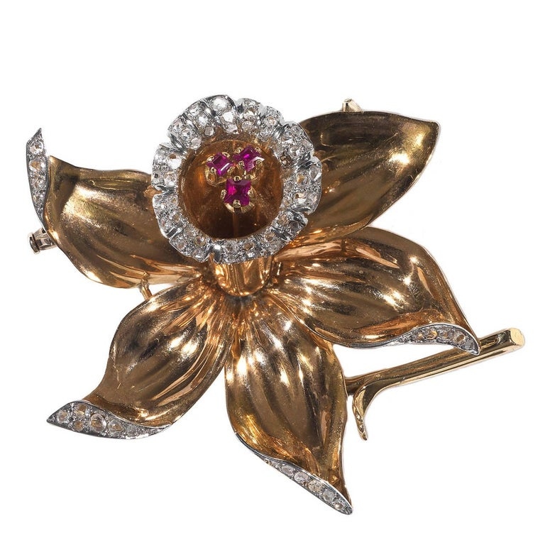 Of flower shape, the borders of the petals and the bud with collet set rose cut diamonds, at the centre of the bud three square cut claw set rubies  Mounted in 18Kt gold and platinum  Weight: 25.3   56 mm high and wide