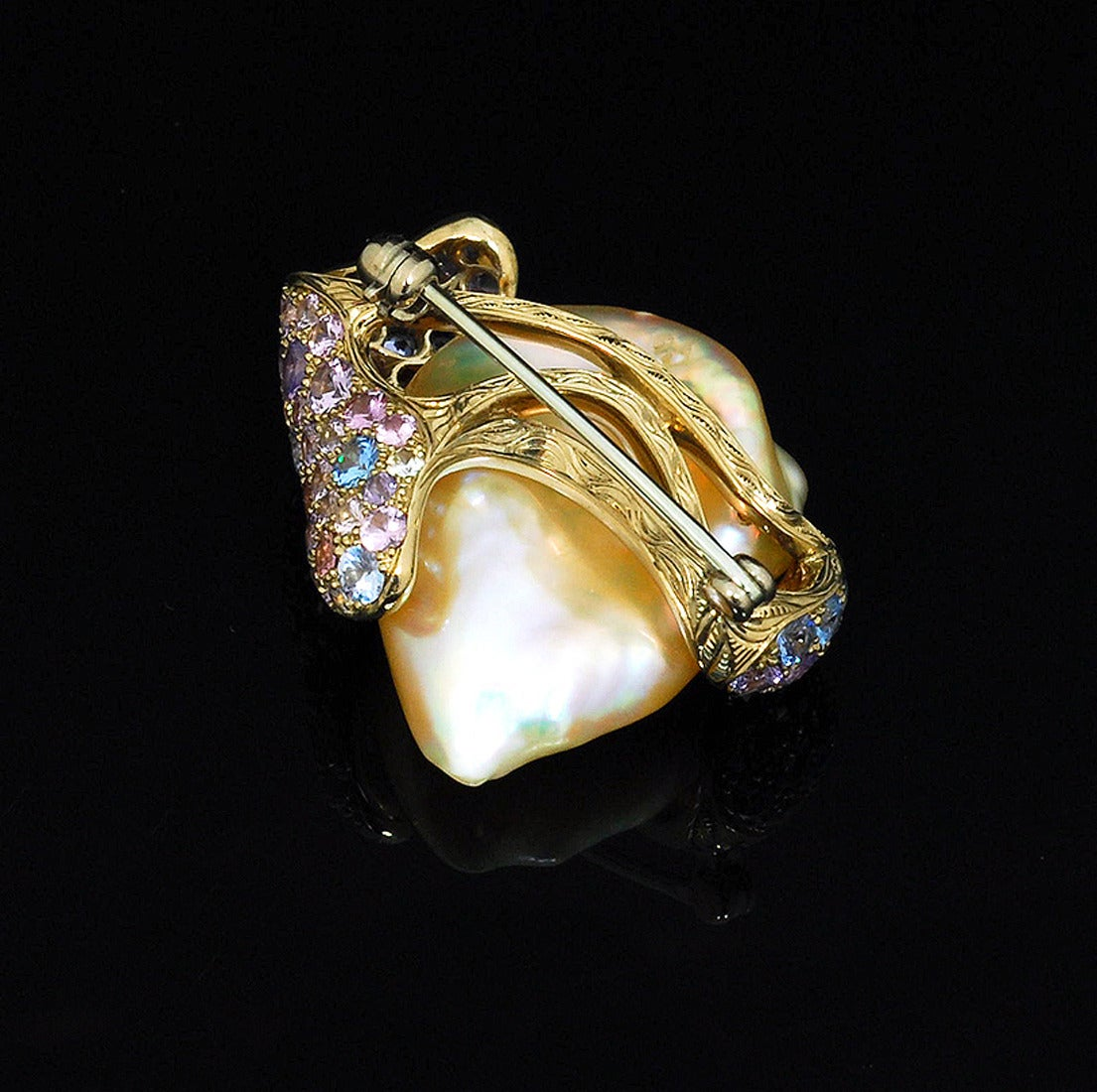 This brooch features a delicate peach Chinese freshwater pearl set in 18K yellow gold, accentuated with an assortment of approximately 66 multicolored diamonds and sapphires.