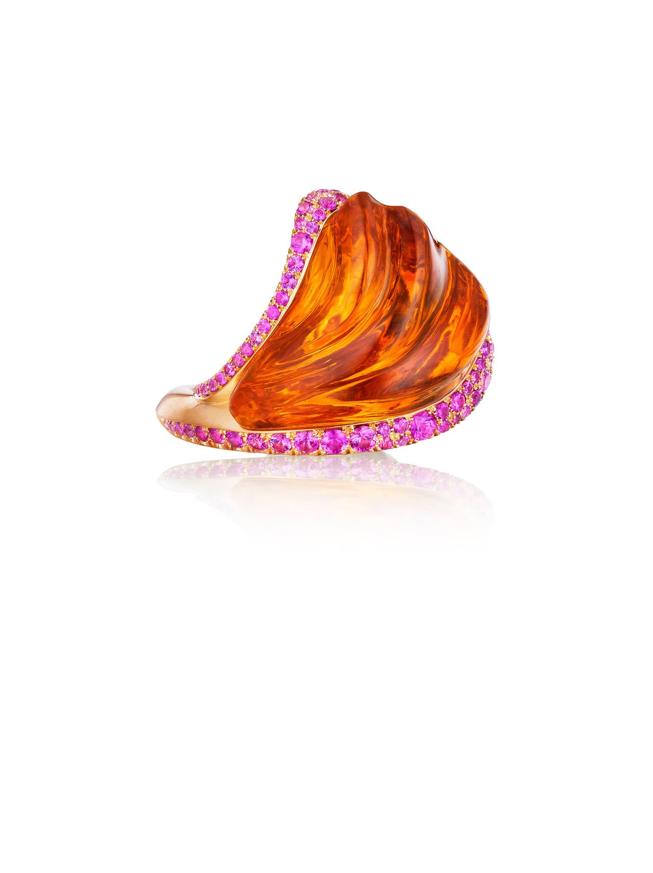 This vibrant ring features a hand-carved 58 ct citrine complimented by hot pink sapphires set in 18K yellow gold.
