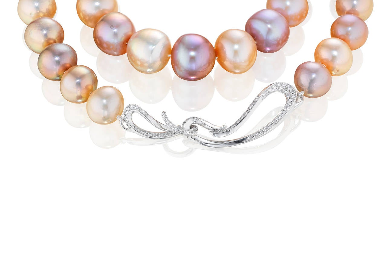 Strand of peach and purple freshwater Pearls (12.5-16.5 mm) finished with our signature clasp. The clasp is 18K White Gold and approximately 1.5 cts of VS-G white diamonds.  Internationally award winning designer Naomi Sarna creates gem carvings and