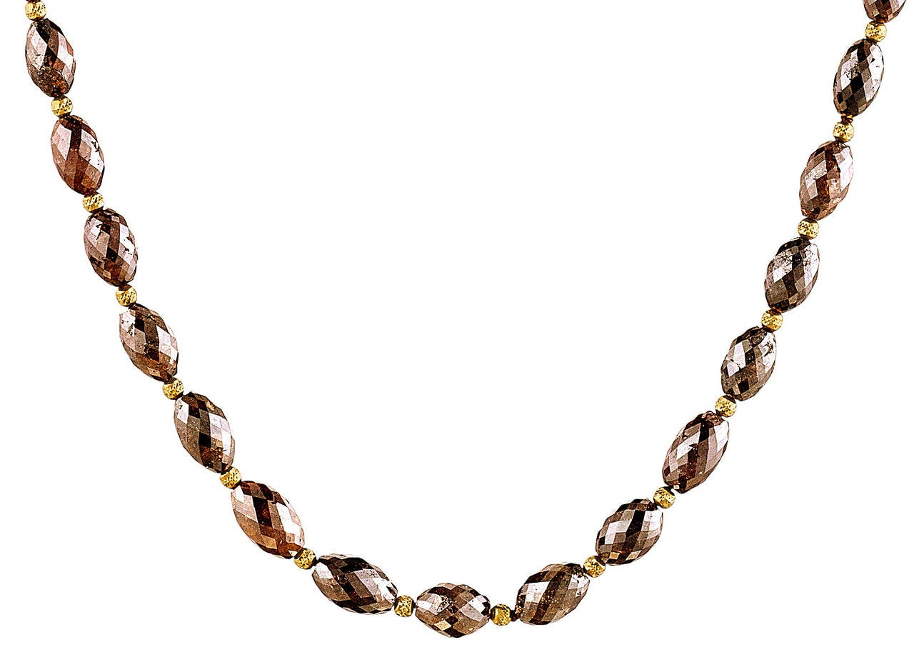 This delicate necklace features an unusual color in diamond necklaces. The dark reddish brown diamonds are approximately 60 ct of 2.8 x 6 - 4.5 x 8 mm beads. They are accentuated by 14K gold spacers and Naomi Sarna's signature 18K yellow gold