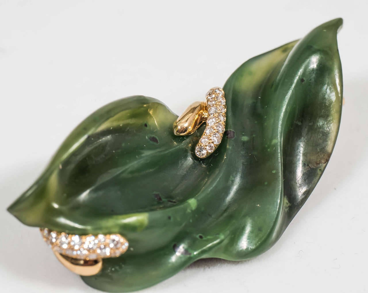 A hand-carved nephrite jade brooch accentuated with 18K yellow gold and 44 VS-F-G white diamonds. The back of the brooch is made of blackened sterling silver.   Internationally award winning designer Naomi Sarna creates gem carvings and jewels of