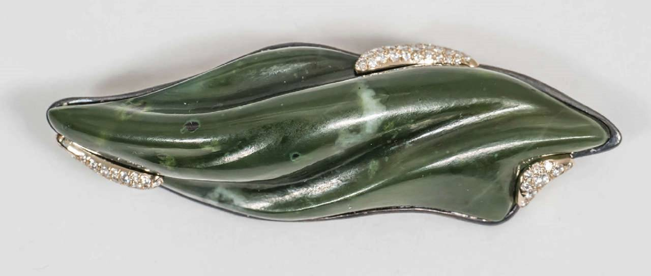 A hand-carved nephrite jade brooch accentuated with 18K yellow gold and 67 VS-FG white diamonds. The back of the brooch is made of blackened sterling silver. 