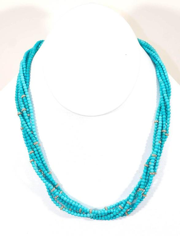 This charming necklace features multiple strands of beautiful turquoise beads from the famous Sleeping Beauty mine in Arizona. It is regarded as some of the finest turquoise in the world. They are accentuated by delicate 18K yellow gold and VS-FG