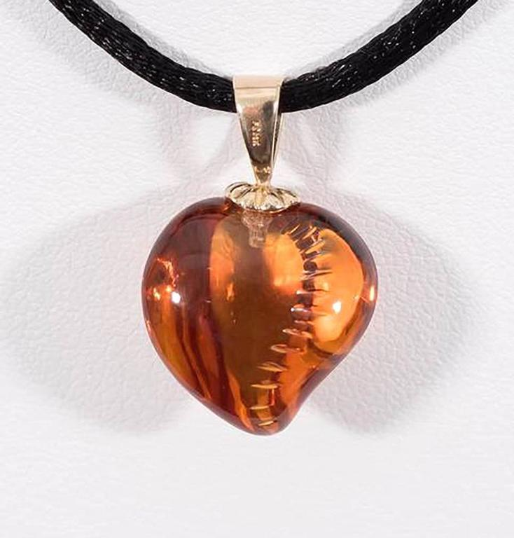 Hand-carved citrine (20 ct) with 18K yellow gold bail.  *listed height includes bail*  Internationally award winning designer Naomi Sarna creates gem carvings and jewels of unusual beauty. She is represented in the Smithsonian's Permanent