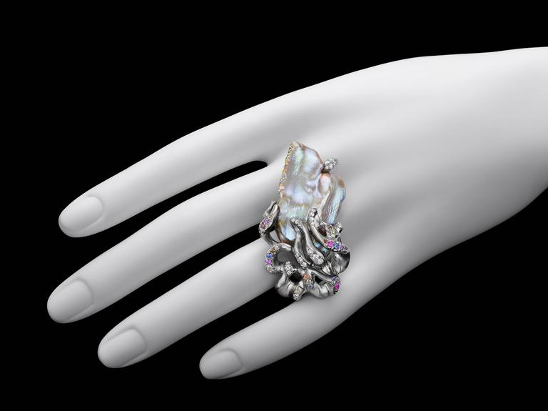 Another fabulous piece in the Caught by a Wave series. Naomi sarna has created a hand-crafted 18K natural palladium white gold ring embracing a Chinese freshwater pearl in iridescent colors that come only from nature. The pearl is complimented by 61