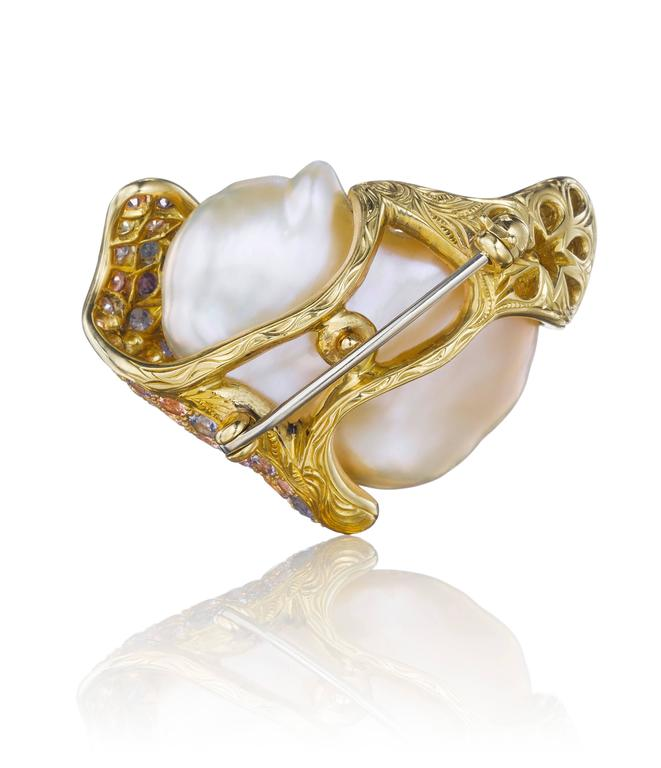 This hand-crafted brooch features a unique Chinese freshwater pearl set in 18K yellow gold, accentuated with an assortment of approximately 66 multicolored diamonds and sapphires.  Internationally award winning designer Naomi Sarna creates gem