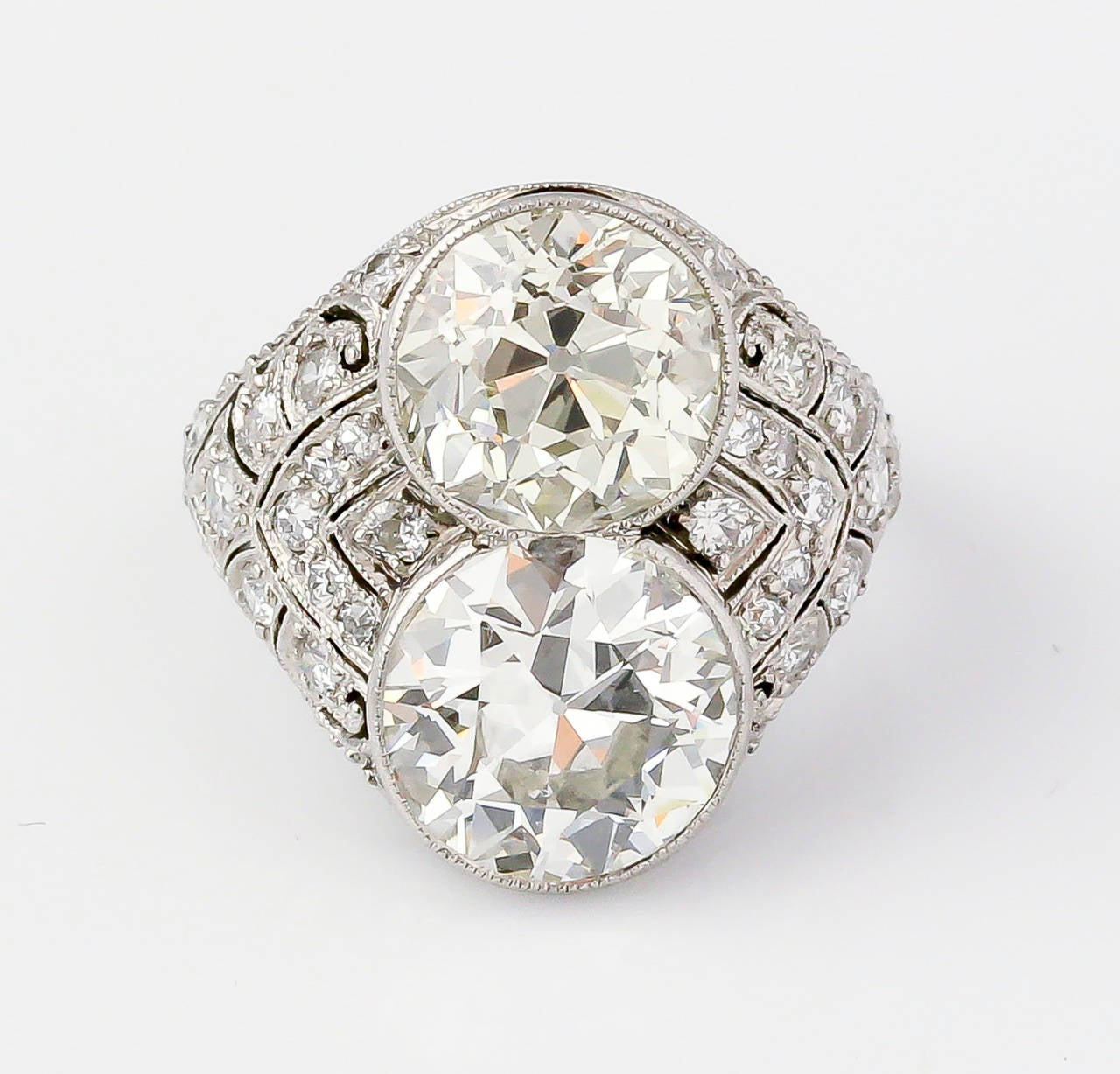 Impressive diamond and platinum cocktail ring from the Art Deco period, circa 1930s. It features two central stones, each approx. 3.5 carats, with high grade round brilliant cut diamonds around the sides.