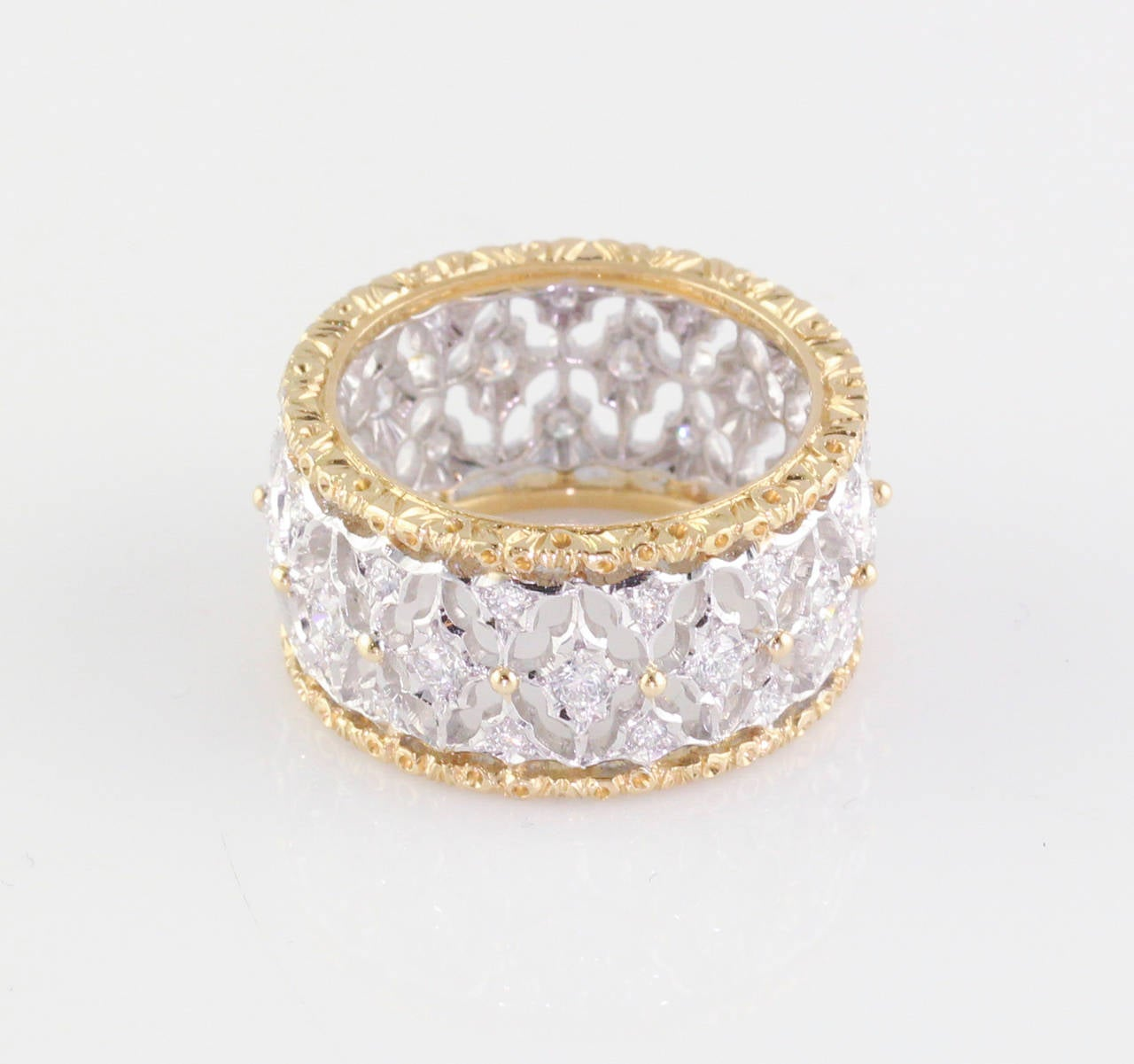 Intricate and elegant diamond band in  18K white and yellow gold, by Mario Buccellati. It features high grade round brilliant cut diamonds, approxl .75cts total weight. Size 6.25.  Hallmarks: M. Buccellati, Italy, 750, Italiant standard mark