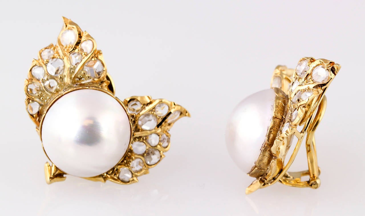 Unsual  18K yellow gold, diamond and Mabe pearl earrings by Buccellati. They feature approx 4-5 carats of rose-cut diamonds of various sizes around a central 15mm diameter Mabe pearl on each earring. Pearls are of very good quality with a lightly