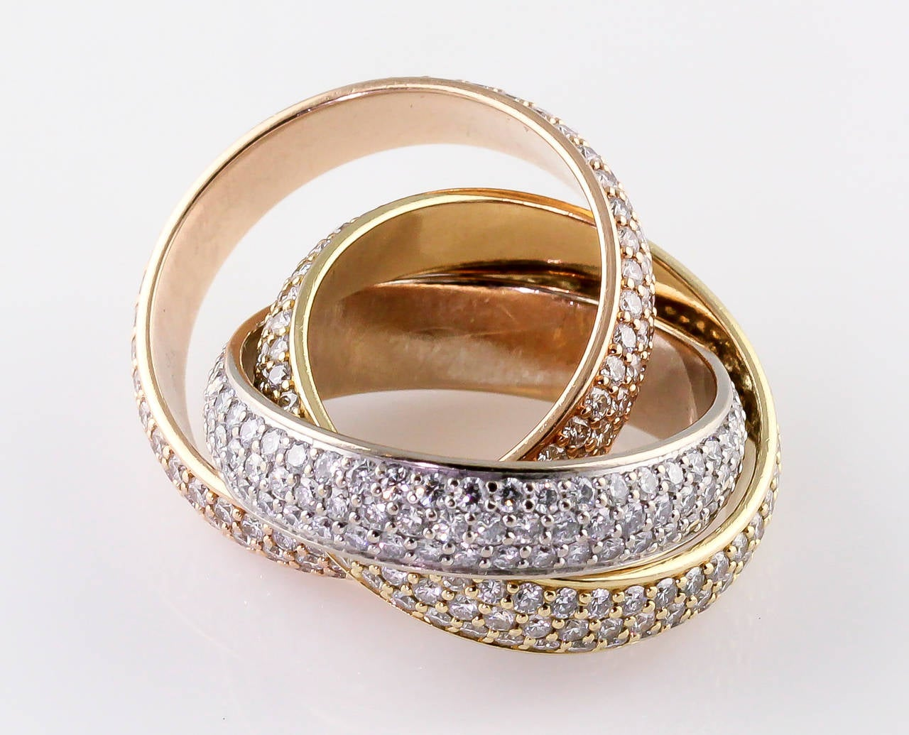 "Elegant and timeless diamond and 18K yellow, white and rose gold rolling ring from the ""Trinity"" collection by Cartier. This model is the ""large"" Trinity pave diamond band.  Current retail $43700. Size 7 (European size 54).