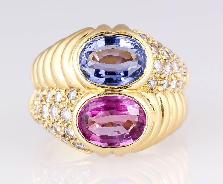 Elegant and vibrant 18K yellow gold, diamond and sapphire ring by Bulgari, circa 1980s. It features two central sapphires: the blue one is oval cut and approx. 2.15cts total weight; the pink one is also oval cut and approx. 1.55cts total weight.