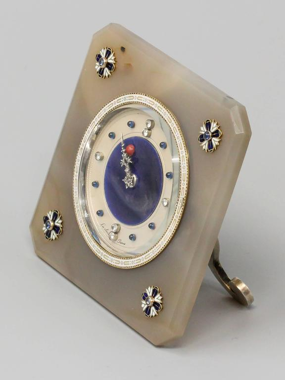 Very rare and unusual desk clock by Lacloche, circa 1920s. Clock features an agate body with white and blue enamel accented at each corner and cabochon blue sapphires on what we believe to be gold. Dial is beautifully made with blue enamel backdrop