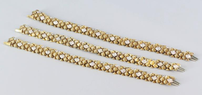 Very fine and bold trio of diamond and 18K yellow gold link bracelets by David Webb. They feature high grade round brilliant cut diamonds, with ribbed links throughout. Beautifully made and a very chic look.   Hallmarks: Webb, 18k.