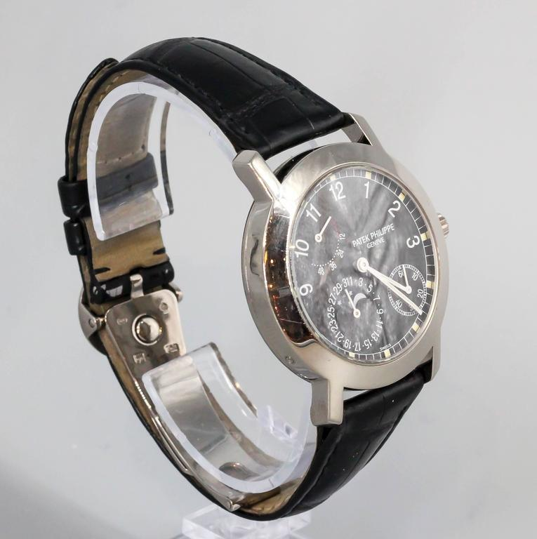 Elegant and refined 18K white gold wristwatch by Patek Philippe, reference #5055G.  Highly intricate watch, with power reserve, moon phase calendar, date,  and is a see-thru skeleton back watch featuring a very fine automatic movement. Comes with
