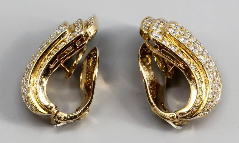Elegant diamond and 18K yellow gold ear clips by Van Cleef & Arpels, circa 1960s-70s. They feature very high grade round brilliant cut diamonds, approx. 5.0-6.0cts total weight. Excellent workmanship and a novel design.