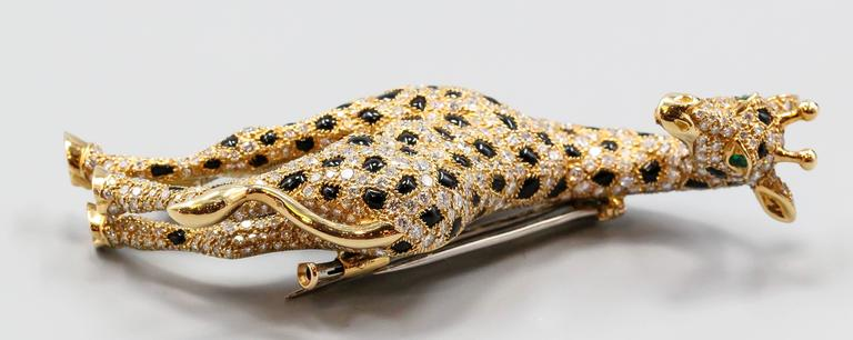 Rare and unusual diamond, emerald, onyx and 18K yellow gold brooch by Cartier. It resembles a giraffe, with high grade round brilliant cut diamonds throughout the body, black onyx spots, emerald eyes and 18K gold setting. Absolutely stunning piece,