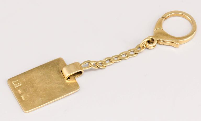 Handsome 18k yellow gold keychain by Dunhill, circa 1960s-70s. It features a rectangular shape with one side textured and the other polished smooth with space for personalized message. With small chain and hook for ease of installation on