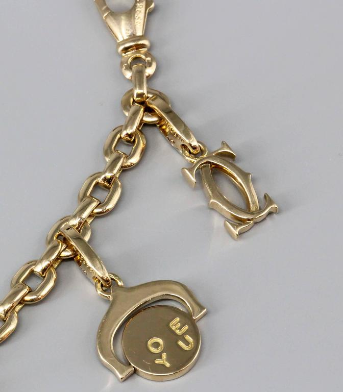 Exceptionally charming 18K yellow gold charm bracelet by Cartier. It features 10 charms, including: trinity ring, Cartier logo, Cartier logo with diamonds, I Love You flip charm, panthere, toy rocking horse, love bracelet, elephant, two-tone gold