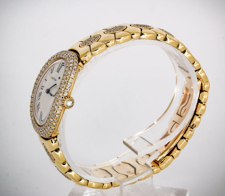 "Chic and rare diamond and 18K yellow gold ladies wrist watch from the ""Baignoire"" collection by Cartier. It features a quartz movement and is water resistant. Factory set high grade round brilliant cut diamonds on the bezel, crown and on"