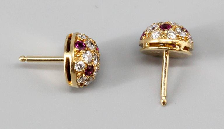 Elegant ruby, diamond and 18K yellow gold stud earrings by Cartier. They feature rich red rubies, along with high grade round brilliant cut diamonds on an 18K yellow gold setting. Impeccable workmanship and easy to wear.  Hallmarks: Cartier, 750,