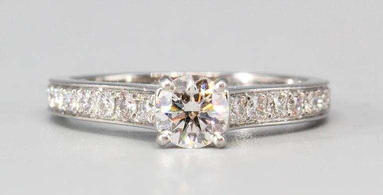 Classic diamond and platinum engagement ring by Cartier. It features high grade round brilliant cut diamonds throughout the sides with a .32ct central stone F color and VS1 clarity, with excellent cut and polish. Beautifully made and highly