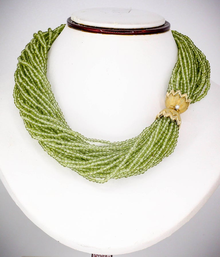Sophisticated diamond, peridot and 18K yellow gold necklace and bracelet combination by Tiffany & Co. Schlumberger. It features interchangeable clasps so you can connect each one to make a larger necklace. Numerous intertwined strands of peridot