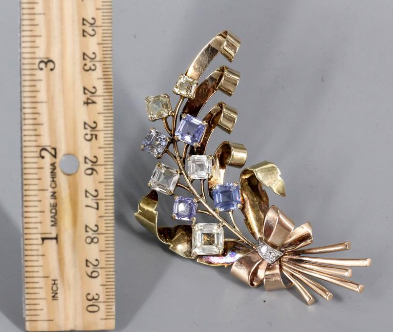 Elegant blue and yellow sapphire brooch, circa 1940s. Set in 14k yellow and pink gold, it features approx. 25 carats of colored sapphires with two round cut diamonds at the base of the brooch. True period piece that makes a statement.