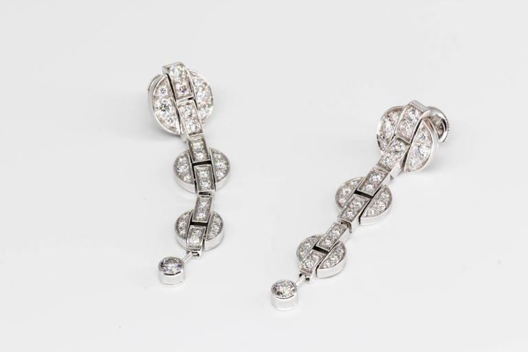 Stylish diamond and 18K white gold drop earrings from the Himalia collection, by Cartier, circa 2006-7. They feature high grade round brilliant cut diamonds, approx. . Beautifully made and very elegant for any occasion.  Hallmarks: Cartier, French