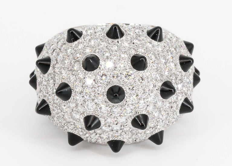 Bold and impressive onyx, diamond and 18k white gold dome ring by Cartier. It features rich black onyx stones fitted like spikes, surrounded by high grade round brilliant cut diamonds throughout, over an 18K white gold setting. Current size 54