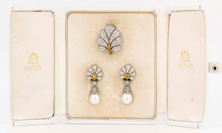 Timeless diamond, pearl, platinum and 18K yellow gold day/night earrings and brooch set by Buccellati, circa 1950s. They feature high grade round brilliant cut diamonds and rich cultured pearls  of approx. 14mm diameter. The earrings can be worn