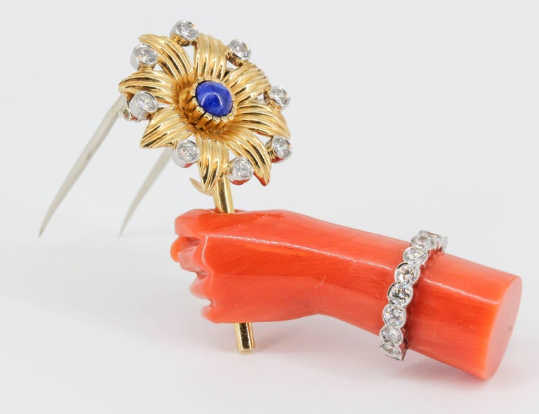 Rare lapis, diamond, platinum, coral and 18K yellow gold brooch by Cartier, of French origin circa 1960s. It resembles a hand holding a flower. The hand is made of rich coral, with high grade round brilliant cut diamonds around it as a bracelet; the