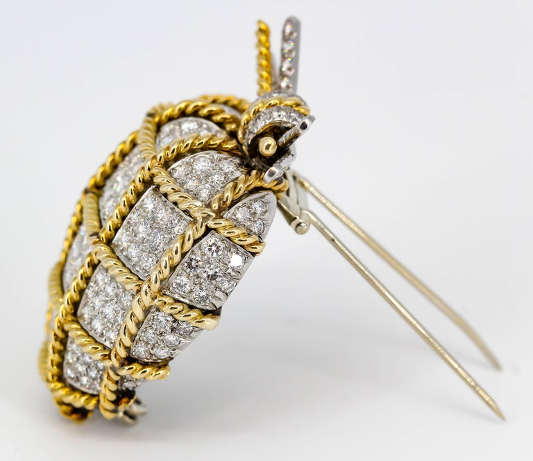 Rare diamond, platinum and 18K yellow gold brooch by Verdura. It features the shape of a diamond encrusted heart, wrapped with a twisted gold rope, and finished off with a bow on top over an overall platinum setting. The diamonds are high grade